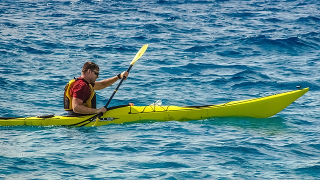 man paddling colorful kayak